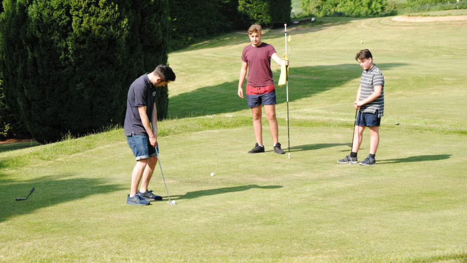3 young teenagers playing pitch and put golf at Bank Farm. They are casually dressed in long shorts and tee shirts. One is about to put the ball on the green, the others stand and watch. The course is well mowed and is surrounded by tall green trees.