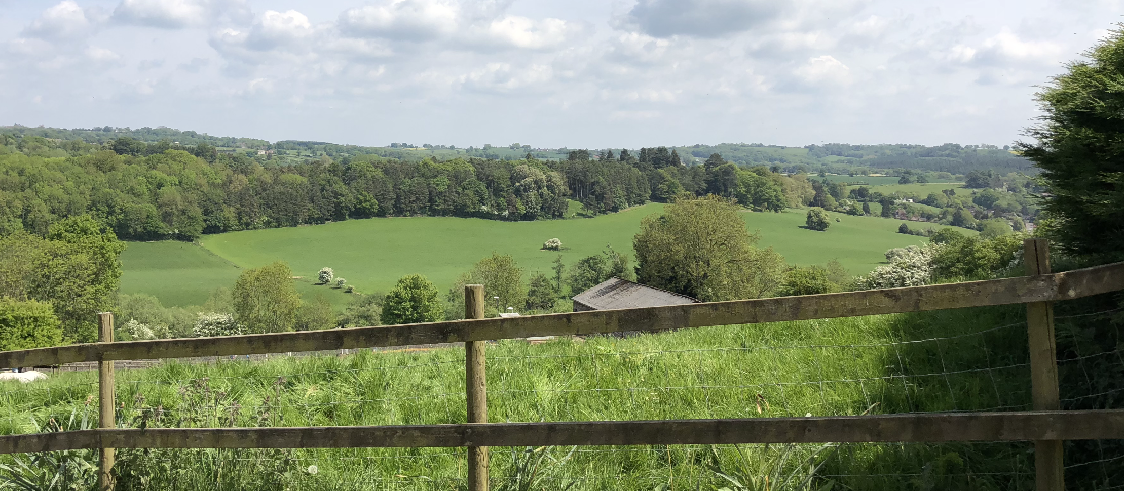 Looking through a railed fence down the Severn valley, it's springtime time, the trees are full of green leaves and blossom, the grass is lush the roof of Bank farm stables can be seen in the valley.