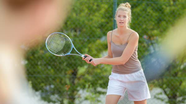A blond lady of about 25 holds a tennis racket ready to receive a ball. Her long hair is in a bun, she's wearing a sleeveless taupe vest top and white short.