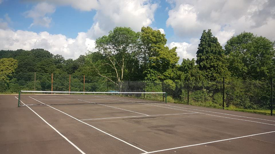 The fenced tarmacked tennis court, clean white lines and nets, edged by tall green trees against a clear blue sky.