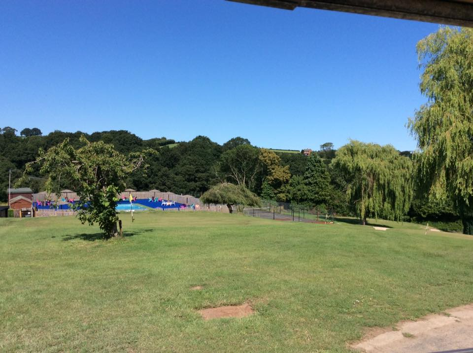 A view across Bank Farm's pitch and put golf course down to the blue AstroTurf edged swimming pool, the pool is securely safety fenced. To the left is the tennis courts and both are surrounded by tall trees on the edge of the Wyre forest. There isn't a cloud in the crystal blue sky.