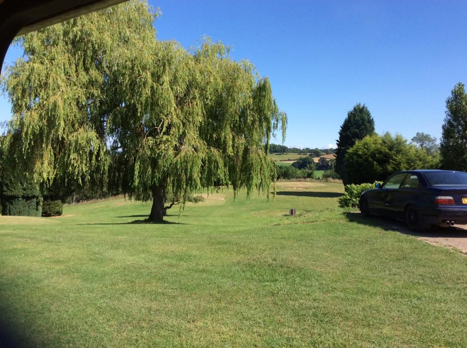 A blue car is parked on the edge of Bank farms pitch and put golf course. The ground falls away and in between the courses greens are a number of trees, a large Willow is central with sculptured Fir trees to the left and right. Beyond the course is a spectacular countryside view down the Severn Valley.