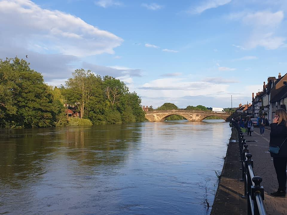 A shop filled street in Bewdley looking down the river Severn towards the tan stone, bridge which spans the river with 3 huge arches. The far side is tree covered with one red building in view.
