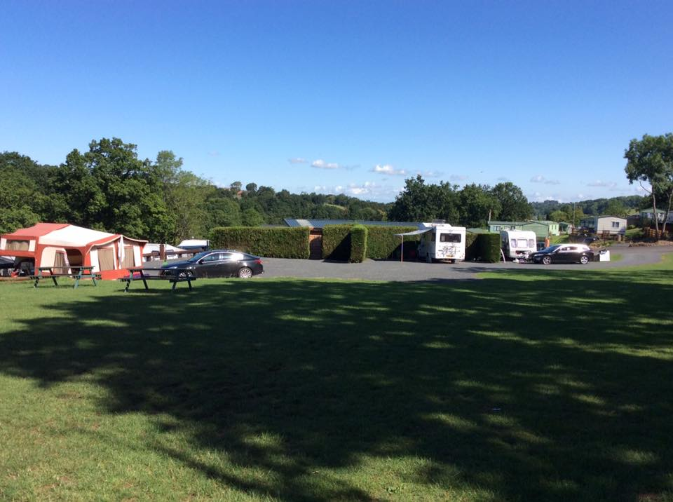 The touring area at Bank Farm Holiday Park with 1 touring caravan, 1 trailer tent and one motorhome and just 2 cars are in view. There's a large green grassy are in the foreground shaded by tall trees. There are 2 picnic benches vacant on the grassy area.
