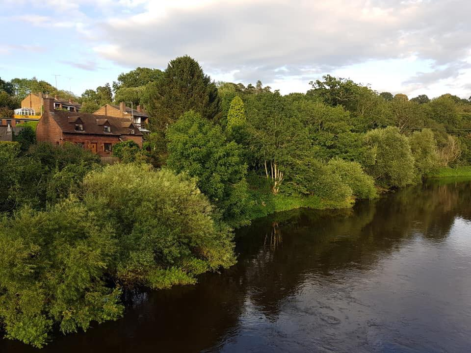 The river Severn as you head into Bewdley, on the far side the trees are in full green leaf and a few red brick houses are dotted around the woodland.