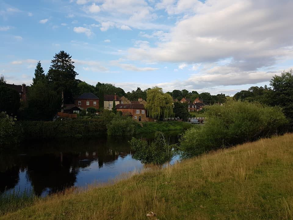 Another view of Arley across the river Severn, the bank this side is steep and grass covered. There are many trees obscuring the few houses that can be seen. The far banks trees and houses are mirrored in the river.