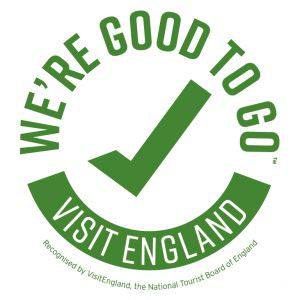 "The ""Visit England"" logo. A green tick surrounded by the words ""We're good to go"" which form a circle with the words ""Visit England"" in reversed type."